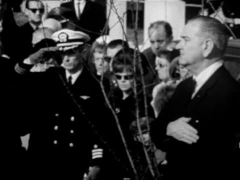 american flag-covered coffin on wagon driving in cemetery during funeral for apollo 1 crew / lyndon johnson with hand over heart and naval officer... - hand on heart stock videos & royalty-free footage