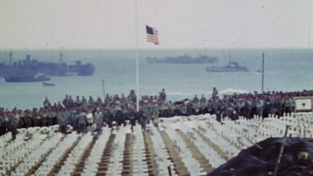 american flags and white crosses marking graves in 3rd marine division cemetery with a firing squad firing volley warships offshore and a marine... - schlacht um iwojima stock-videos und b-roll-filmmaterial