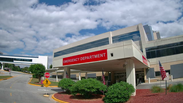 american flags at the entrance of the atlanta va medical center emergency room in atlanta, georgia on may 31, 2021 - directional sign stock videos & royalty-free footage