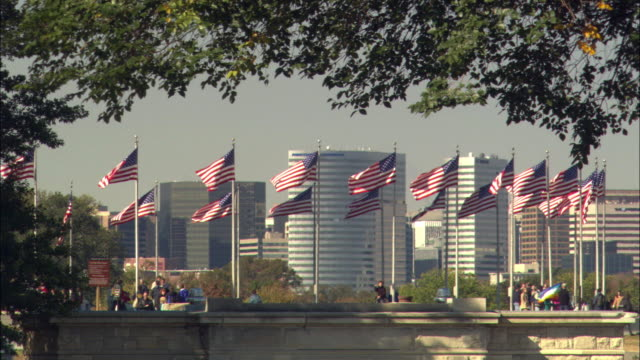 vídeos de stock e filmes b-roll de ws american flags flapping on wind, skyscrapers in background / rosslyn, virginia, usa - arlington virgínia