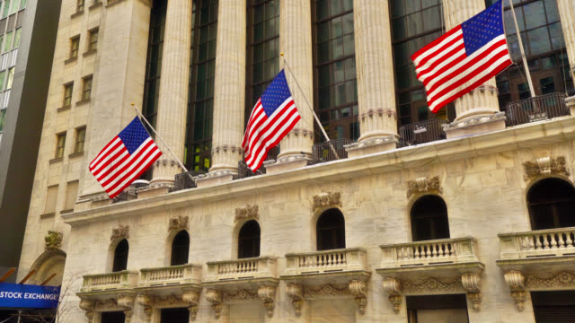 american flags hung on stock exchange building in wall street. - wall street crash of 1929 stock videos & royalty-free footage