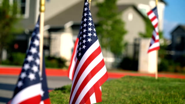 american flags in front of suburb apartment complex - veteran stock videos & royalty-free footage