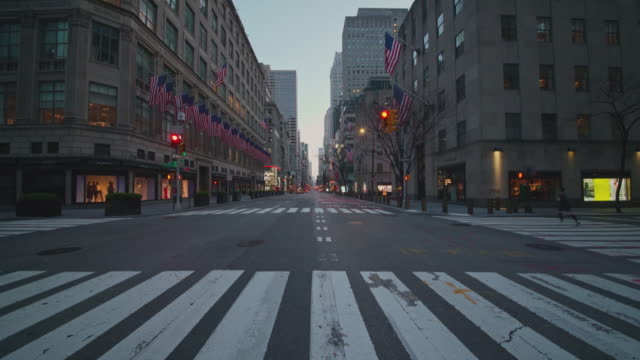 amerikanska flaggor på 5th avenue, en av de mest trånga destinationer i new york city, som överges på grund av covid-19 pandemiutbrott. - arbetslöshet bildbanksvideor och videomaterial från bakom kulisserna