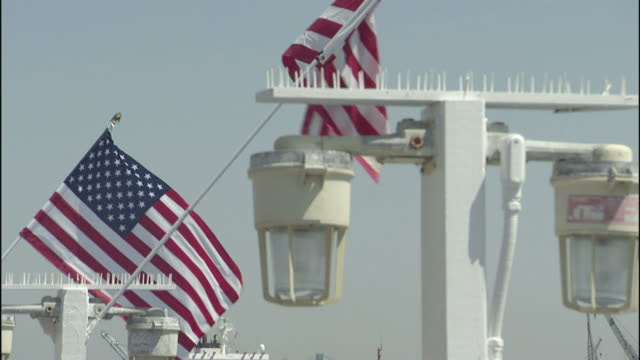 American flags wave above a dock where a barge and tugboat pass in Los Angeles.