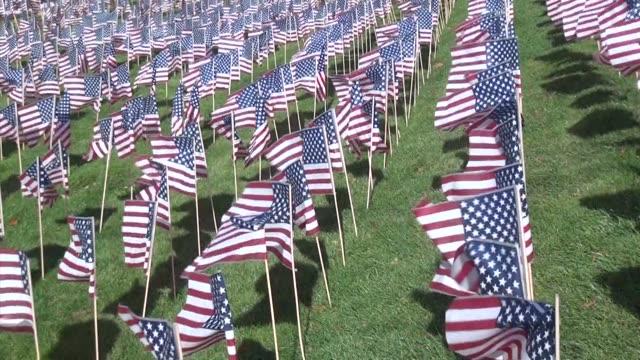 vidéos et rushes de american flags wave on high school field - salmini