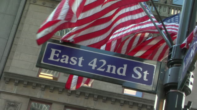 CU American flags waving in wind behind East 42nd Street sign / New York, New York, USA