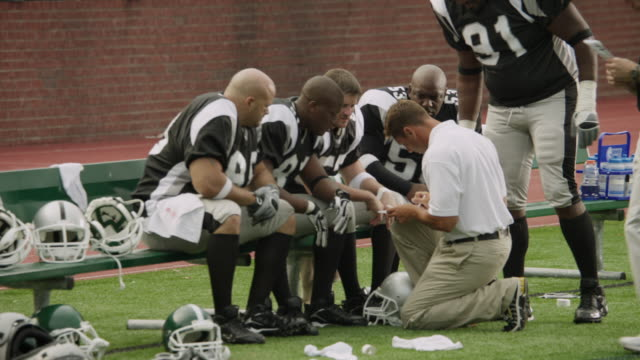 ms, american football coach talking to players on bench, staten island, new york, usa - kneeling stock videos and b-roll footage