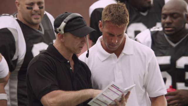 cu, american football coach talking to players on sidelines, staten island, new york, usa - アメフトのユニフォーム点の映像素材/bロール