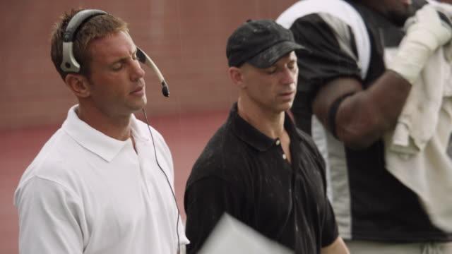 cu, pan, american football coach talking to players on sidelines, staten island, new york, usa - アメフトのユニフォーム点の映像素材/bロール