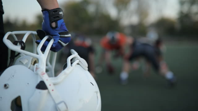 american football helmet in a mans hand - american football ball stock videos & royalty-free footage