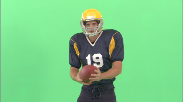 ms, american football player catching and throwing ball in studio, portrait - neenah stock videos & royalty-free footage