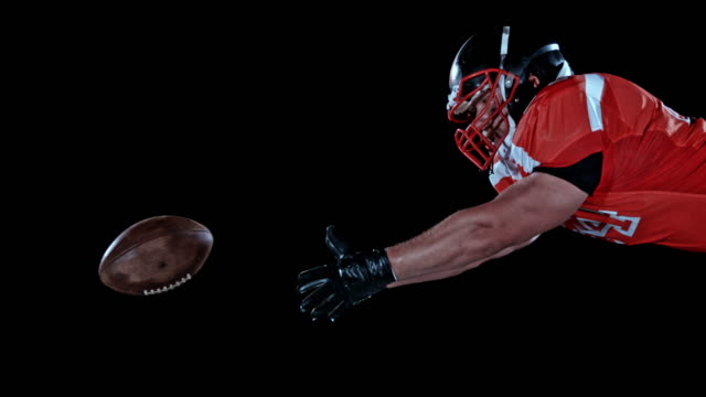 slo mo ld american football player catching the ball while airborne - sports glove stock videos and b-roll footage