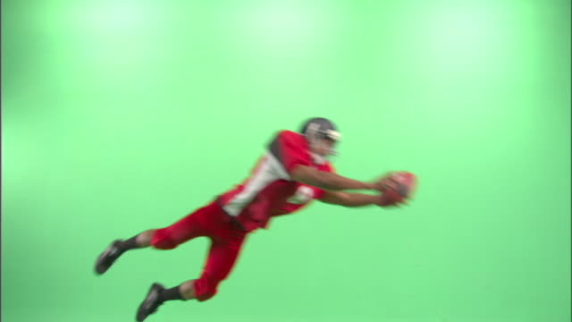 ws, american football player diving and catching football ball in studio - wide shot stock videos & royalty-free footage