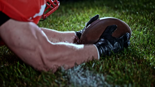 slo mo american football player falling to the ground while holding the ball in his hands - american football sport stock videos & royalty-free footage