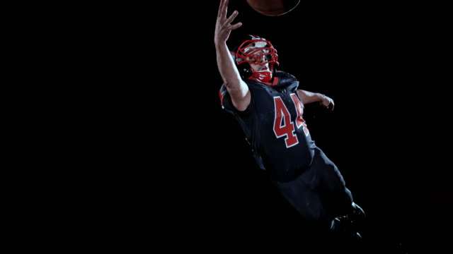 slo mo american football player in black jersey catching the ball in the air with one hand on black background - catching stock videos & royalty-free footage