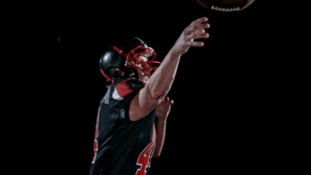 speed ramp american football player in black jersey throwing the ball on black background - american football player stock videos & royalty-free footage