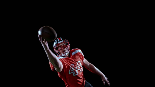 speed ramp american football player in red jersey catching the ball with one hand on black background - american football ball stock videos & royalty-free footage