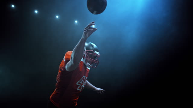 SLO MO American football player in red jersey throwing the ball at night