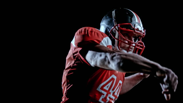 speed ramp american football player in red jersey throwing the ball on a black background - american football ball stock videos & royalty-free footage