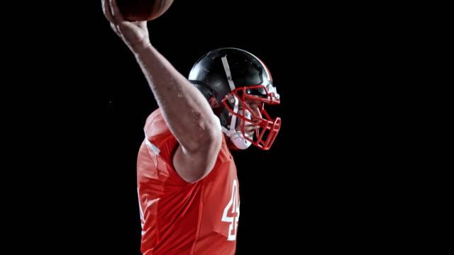 DREHZAHLRAMPE American-Football-Spieler in roten Trikots wirft den Ball auf schwarzem Hintergrund