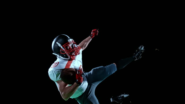 slo mo american football player in white jersey catching the ball in the air with one hand on black background - american football ball stock videos & royalty-free footage