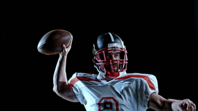 speed ramp american football player in white jersey throwing the ball on a black background - american football ball stock videos & royalty-free footage