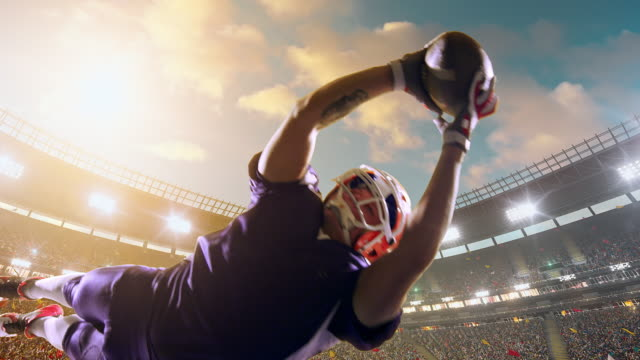 vídeos de stock e filmes b-roll de american football player jumps with a ball - futebol americano