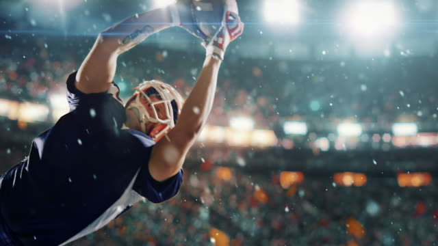 vídeos de stock e filmes b-roll de american football player jumps with a ball - football