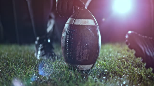 slo mo american football player kicking the ball held by his teammate on the field at night - calcio sport video stock e b–roll