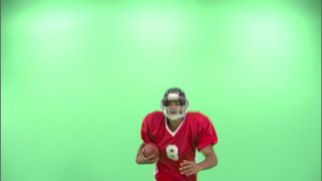 ms, cu, american football player running and jumping in studio - アメフトのユニフォーム点の映像素材/bロール