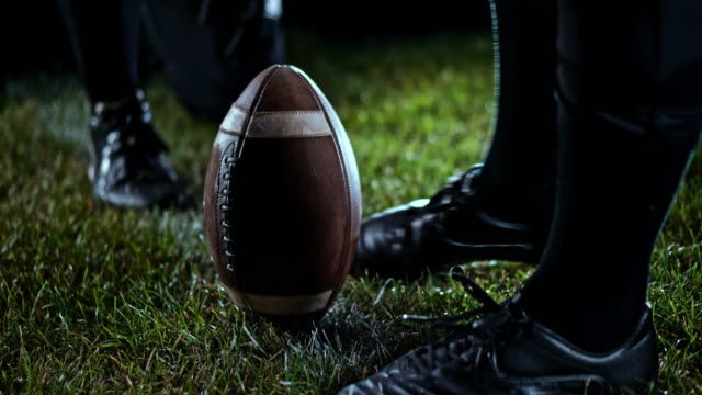 slo mo american football player taking a place kick - kicking stock videos & royalty-free footage