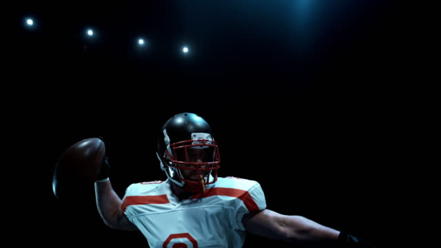 speed ramp american football player throwing the ball at night - 投げる点の映像素材/bロール