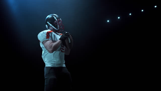 slo mo american football player throwing the ball at night - 投げる点の映像素材/bロール