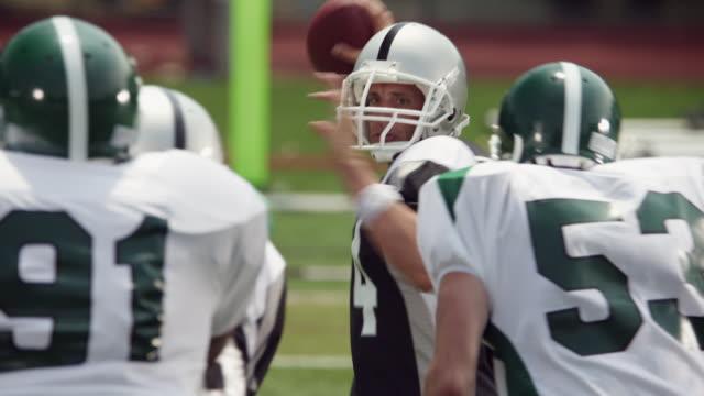 slo mo, cu, focusing, american football players in action, staten island, new york, usa - クオーターバック点の映像素材/bロール