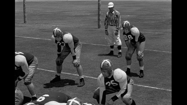 vidéos et rushes de american football players line up and run play american football game on january 01 1942 - couvre chef