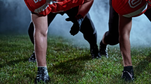 SLO MO American football players positioned on the field at night with mist in the background
