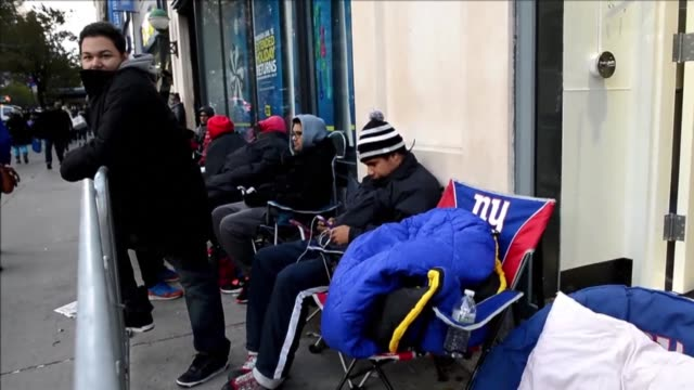 vídeos de stock, filmes e b-roll de american gamers started waiting in line in front of electronics stores to purchase sonys new playstation 4 video game console at its midnight launch... - meia noite