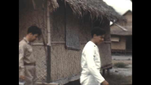 american gi's walk past their living quarters consisting of thatched huts. they are holding metal food trays in their hands. - strohdach stock-videos und b-roll-filmmaterial
