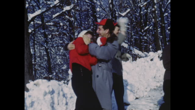 vídeos de stock, filmes e b-roll de american home movie footage circa 1950 of a group of friends messing around in the snow - 1950