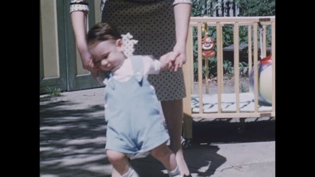 american home movie footage circa 1950 of a toddler learning to walk, helped by his mother. - 社会史点の映像素材/bロール