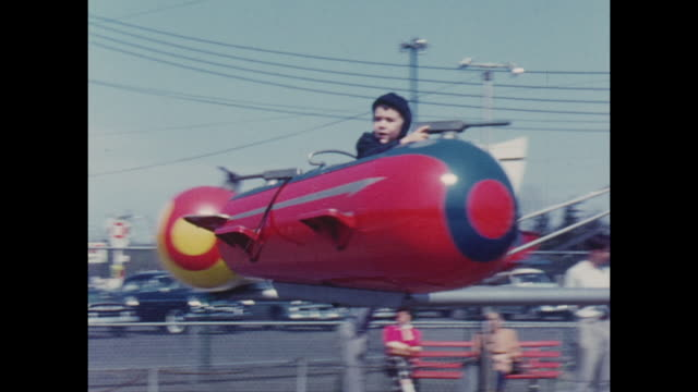 american home movie footage circa 1950 of young boys on various fairground rides - vergangenheit stock-videos und b-roll-filmmaterial