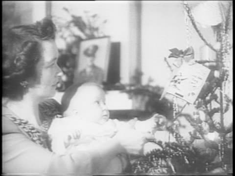 vídeos de stock e filmes b-roll de american houses in neighborhood along a curved street / montage of family gathered around a fire and christmas tree enjoying gifts mother looking at... - 1944
