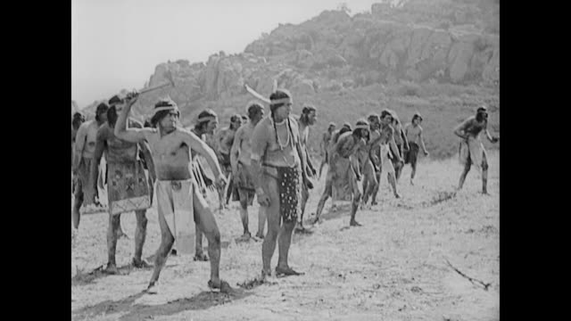 1922 American Indian army surrounds man (Buster Keaton) in top hat and tails