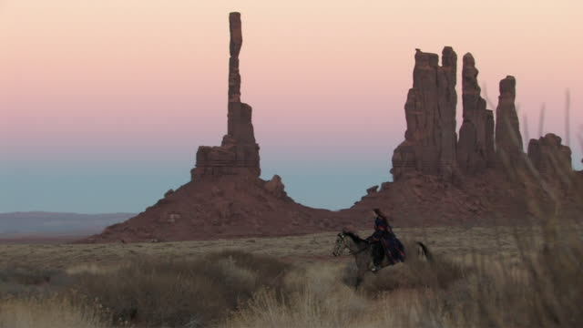 ws, pan, american indian man riding horse in monument valley navajo tribal park, utah, usa - nordamerikanisches indianervolk stock-videos und b-roll-filmmaterial