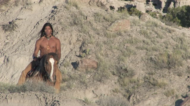 stockvideo's en b-roll-footage met ms zo american indian man riding horse in new mexico desert canyons at sunset / santa fe, new mexico, united states - duurzaam toerisme
