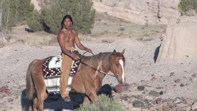 vídeos de stock e filmes b-roll de ms american indian man riding horse in new mexico desert canyons / santa fe, new mexico, united states - ecoturismo