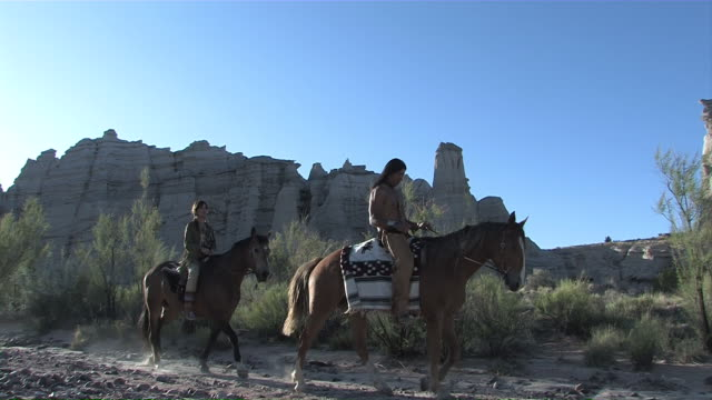MS PAN American Indian Native Couple Horse Back Riding in spectacular Rocky New Mexico canyon / Santa Fe, New Mexico, United States