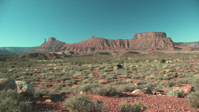 vidéos et rushes de ws, american indian woman riding horse in red desert, utah, usa - ouest américain