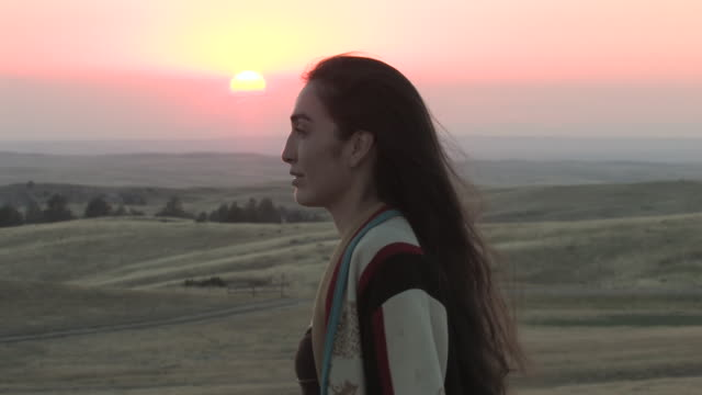 vídeos de stock e filmes b-roll de cu zo american indian young woman standing on great plains at sunset time / pine ridge, south dakota, united states    - cultura tribal da américa do norte