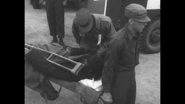 american korean war pow carried on stretcher during munsan prisoner exchange/ soldier with ptsd / man standing over and talking to man on stretcher... - prisoner of war stock videos & royalty-free footage
